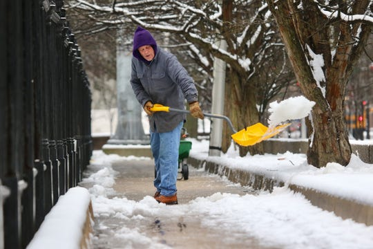 Mark Bivens, a maintenance worker at Brandywine Wilmington Cemetery, shovels snow.