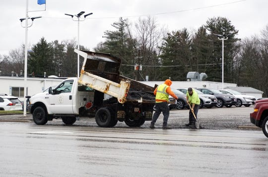 A City of Zanesville street department pothole crew dodges traffic on Maple Avenue Tuesday afternoon.