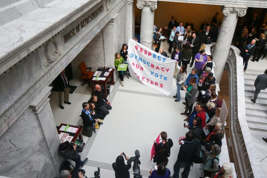 A group of people protest Utah's plan to scale back a voter-approved Medicaid expansion inside the State Capitol in Salt Lake City.