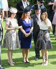 Princess Eugenie and Princess Beatrice flank their mother, Sarah Ferguson the  Duchess of York at Royal Ascot at Ascot Racecourse on June 19, 2015.