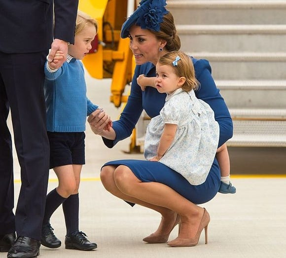 The Duchess of Cambridge showing her parenting technique with Prince George while holding Princess Charlotte.