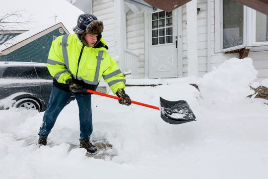 Patrick Cain, of Manitowoc, Wis., shovels out his entryway as snow blankets the area Feb. 12, 2019.