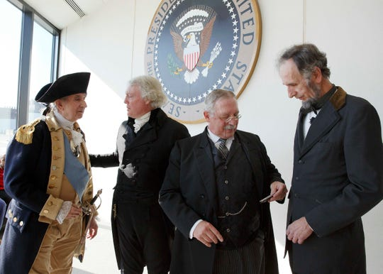 Actors portraying past U.S. presidents, from left, George Washington, Thomas Jefferson, Theodore Roosevelt and Abraham Lincoln stand in front of the Presidential Seal during a past Presidents Day festival at the John F. Kennedy Library in Boston.