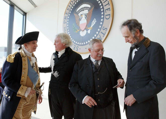 Actors portraying past U.S. presidents, from left, George Washington, Thomas Jefferson, Theodore Roosevelt and Abraham Lincoln stand in front of the Presidential Seal during a past Presidents' Day festival at the John F. Kennedy Library in Boston.