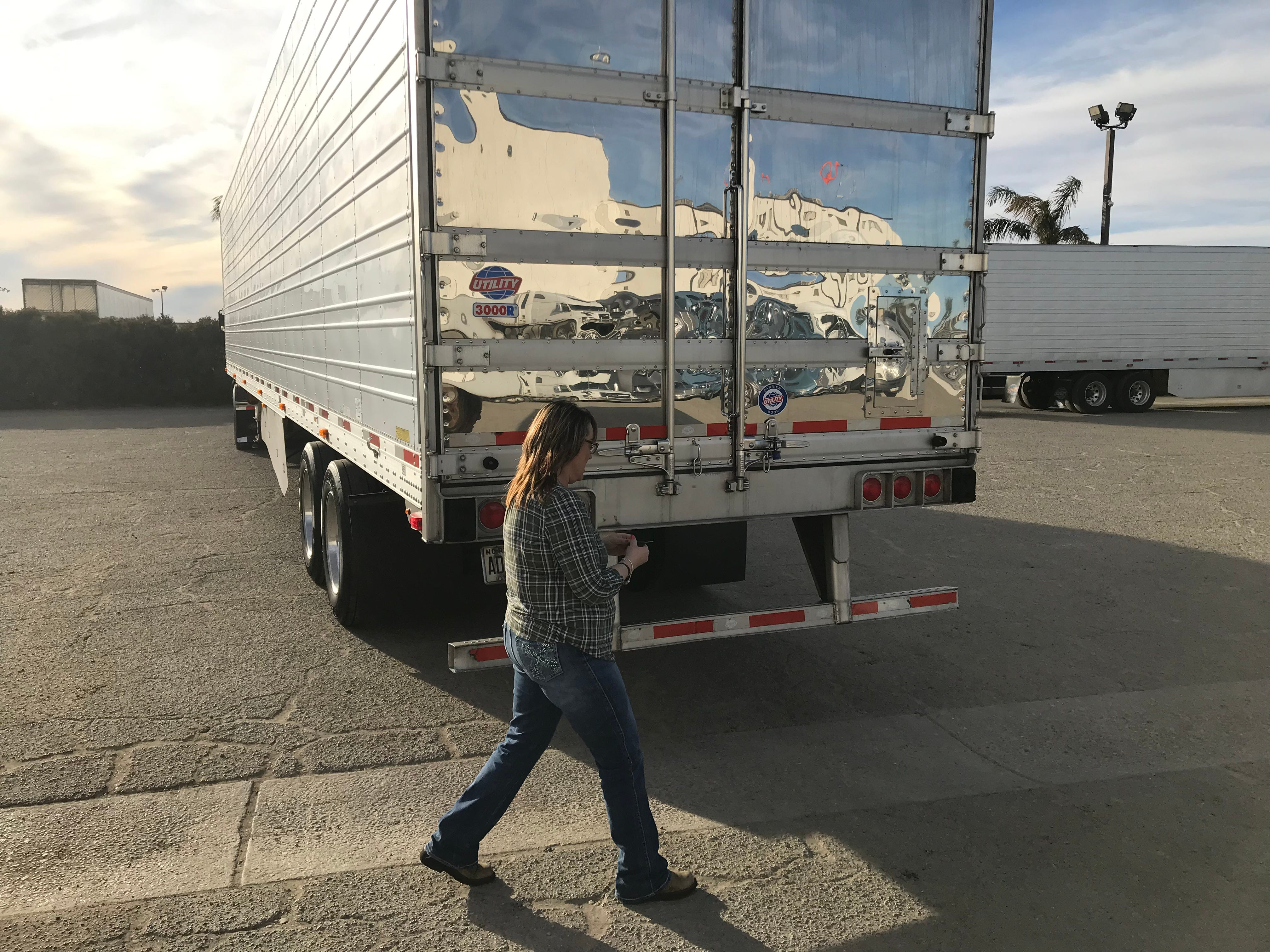 Ingrid Brown walks around back to open the trailer of her big rig