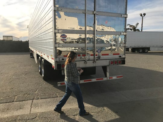 Ingrid Brown walks around back to open the trailer of her big rig.
