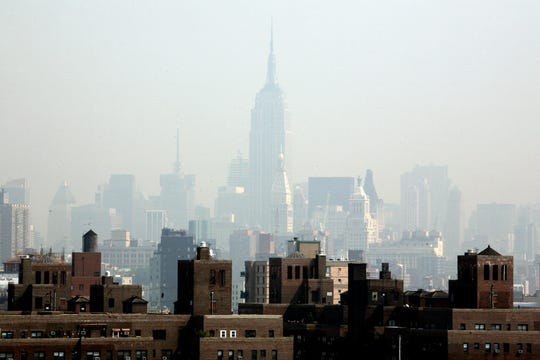 Smog covers midtown Manhattan in New York on Tuesday, July 10, 2007. By 2080, the climate of New York will be similar to that of Arkansas today.