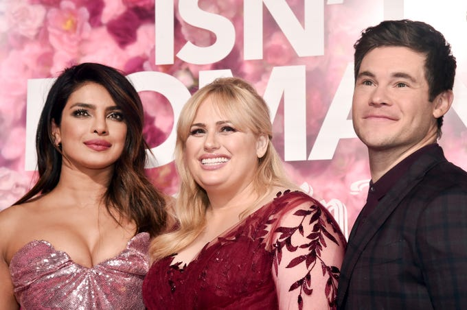 "LOS ANGELES, CALIFORNIA - FEBRUARY 11: (L-R) Priyanka Chopra, Rebel Wilson, and Adam DeVine attend the premiere of Warner Bros. Pictures' ""Isn't It Romantic"" at The Theatre at Ace Hotel on February 11, 2019 in Los Angeles, California. (Photo by Alberto E. Rodriguez/Getty Images) ORG XMIT: 775292839 ORIG FILE ID: 1129043373"