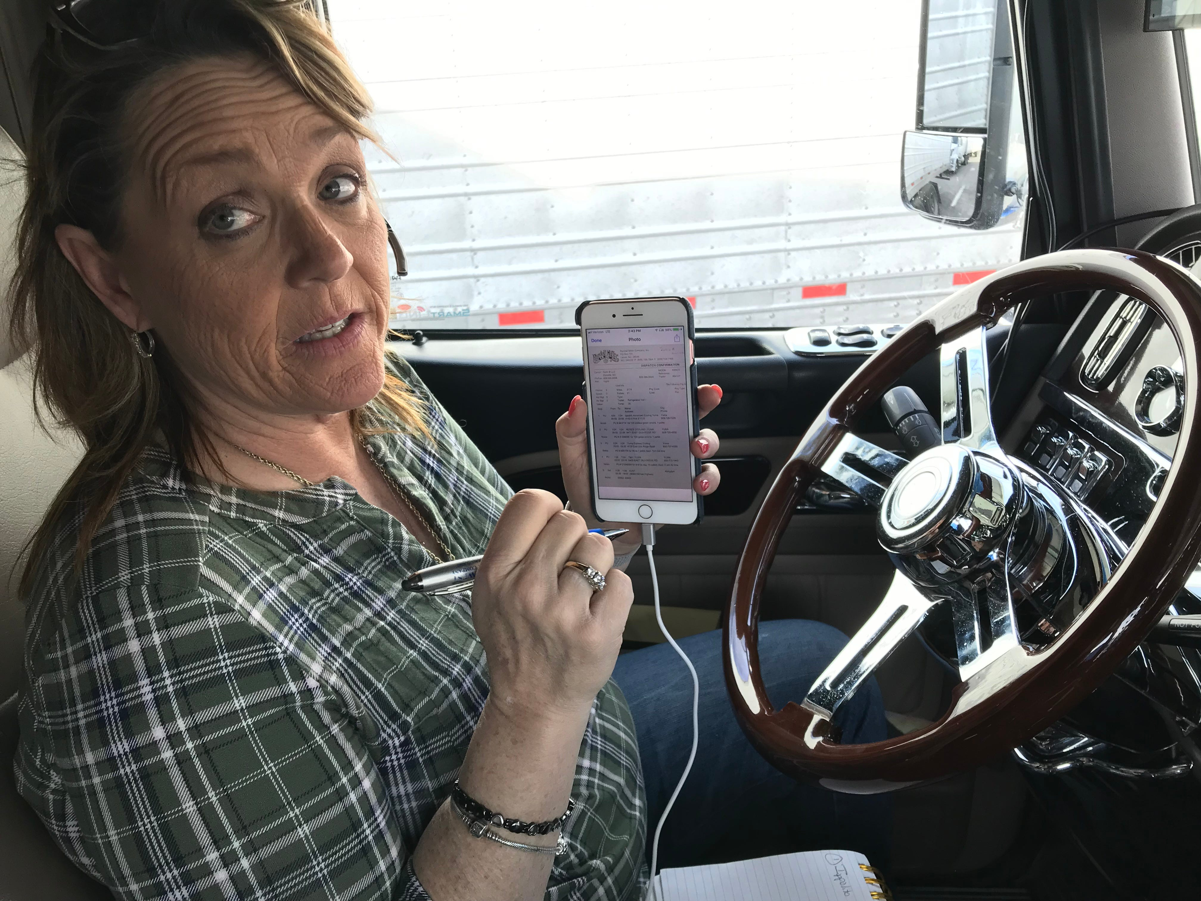 Ingrid Brown checks on navigation data from her phone behind the wheel of her big rig.