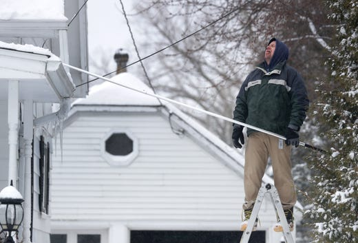 Jason Griffith takes a break from clearing snow off of the roof of his house and to catches a snowflake on his tongue, Feb. 12, 2019, in Little Chute, Wis.