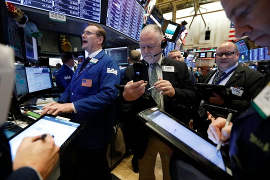 Specialist Patrick King, left, works with traders at his post on the floor of the New York Stock Exchange, Tuesday, Feb. 12, 2019. U.S. stocks are gaining in early trading after U.S. lawmakers reached a tentative deal to avoid another costly government shutdown.