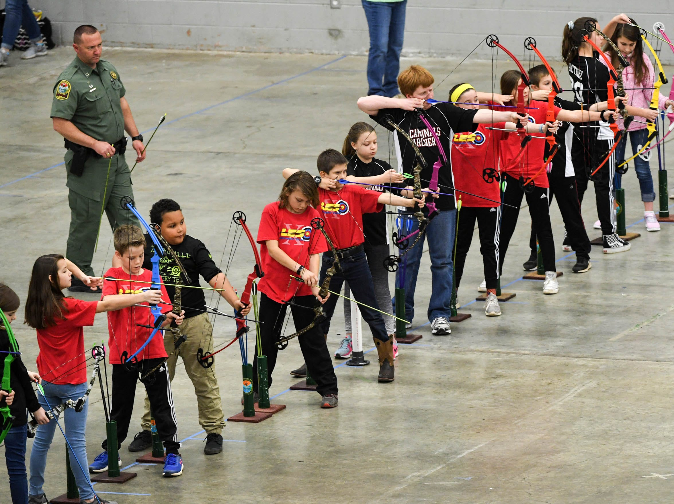 Sfc. Ken Cope watches over students ready to release an arrow during the South Carolina Department of Natural Resources regional National Archery in the Schools Program (NASP) regional competition at the Anderson Civic Center Wednesday.  The program, which awards $50,000 in scholarships to high school seniors, is a joint venture between state departments of Education and Wildlife. The competition in Anderson, leading up to the state finals March 26-28 in Sumter, had 950 children from 14 elementary and 23 high schools around the state. Pendelton High School finished first in the IBO competition and second in the bullseye for the high school division, Riverside Middle School in Pendleton finished first in the IBO and bullseye competitions for middle schools, and LaFrance Elementary team finished first.