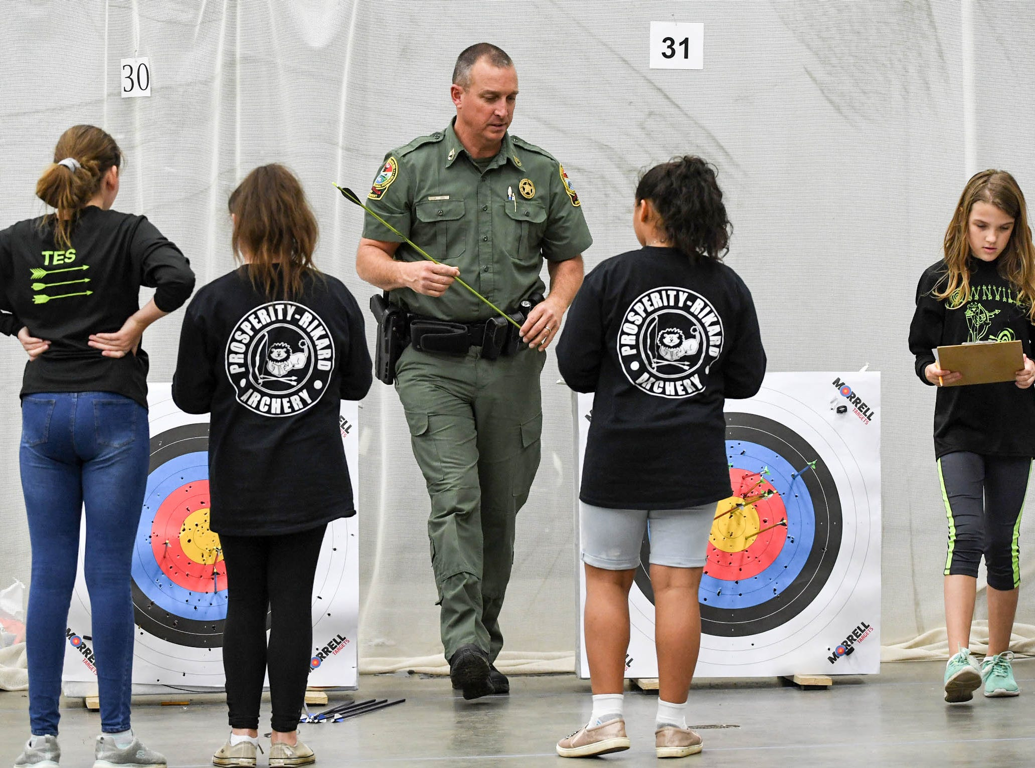 Sfc. Ken Cope, left, helps teach students during the South Carolina Department of Natural Resources regional National Archery in the Schools Program (NASP) regional competition at the Anderson Civic Center Wednesday.