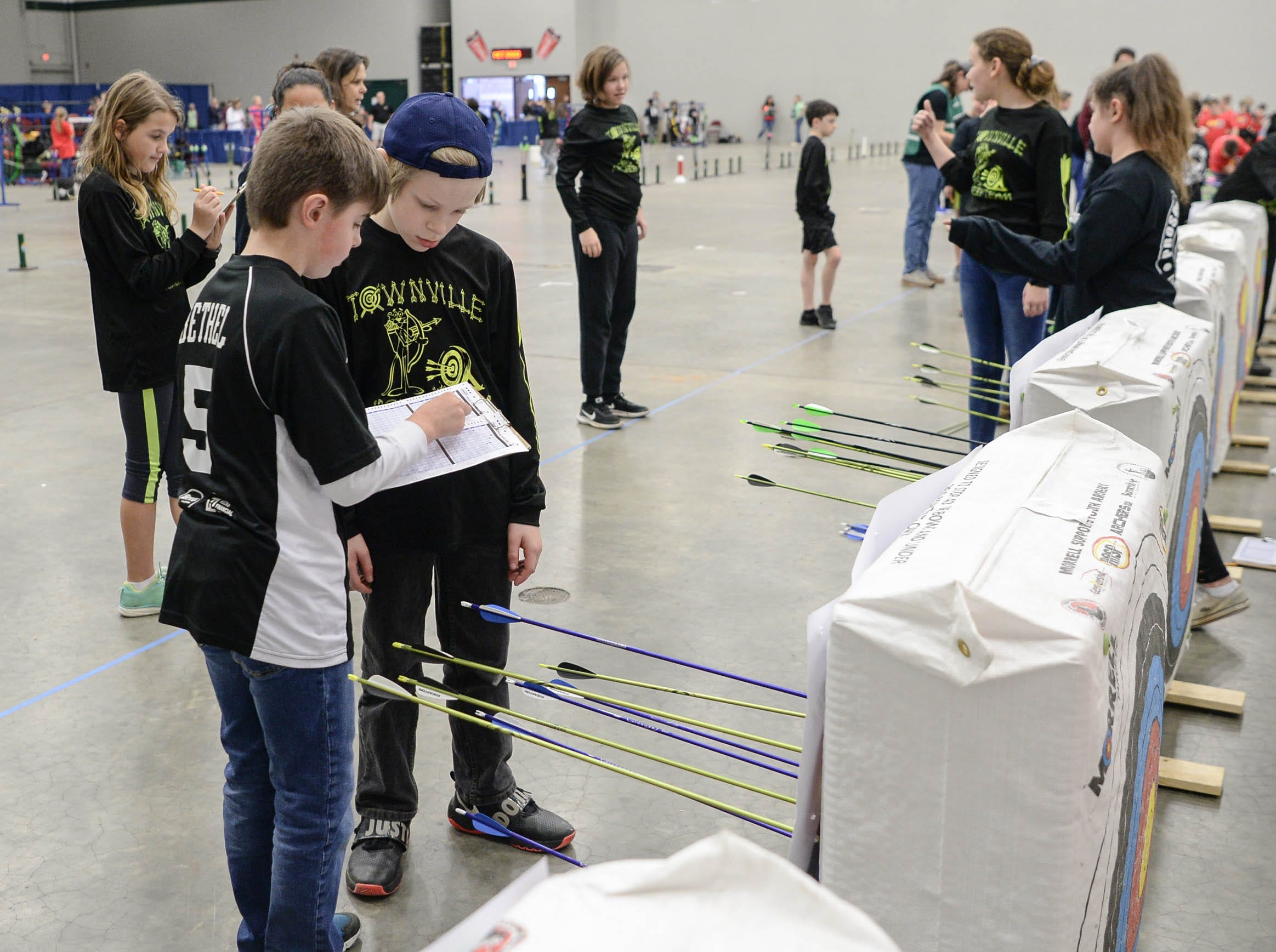 Students tally points after shooting their arrows during the South Carolina Department of Natural Resources regional National Archery in the Schools Program (NASP) regional competition at the Anderson Civic Center Wednesday.  The program, which awards $50,000 in scholarships to high school seniors, is a joint venture between state departments of Education and Wildlife. The competition in Anderson, leading up to the state finals March 26-28 in Sumter, had 950 children from 14 elementary and 23 high schools around the state.