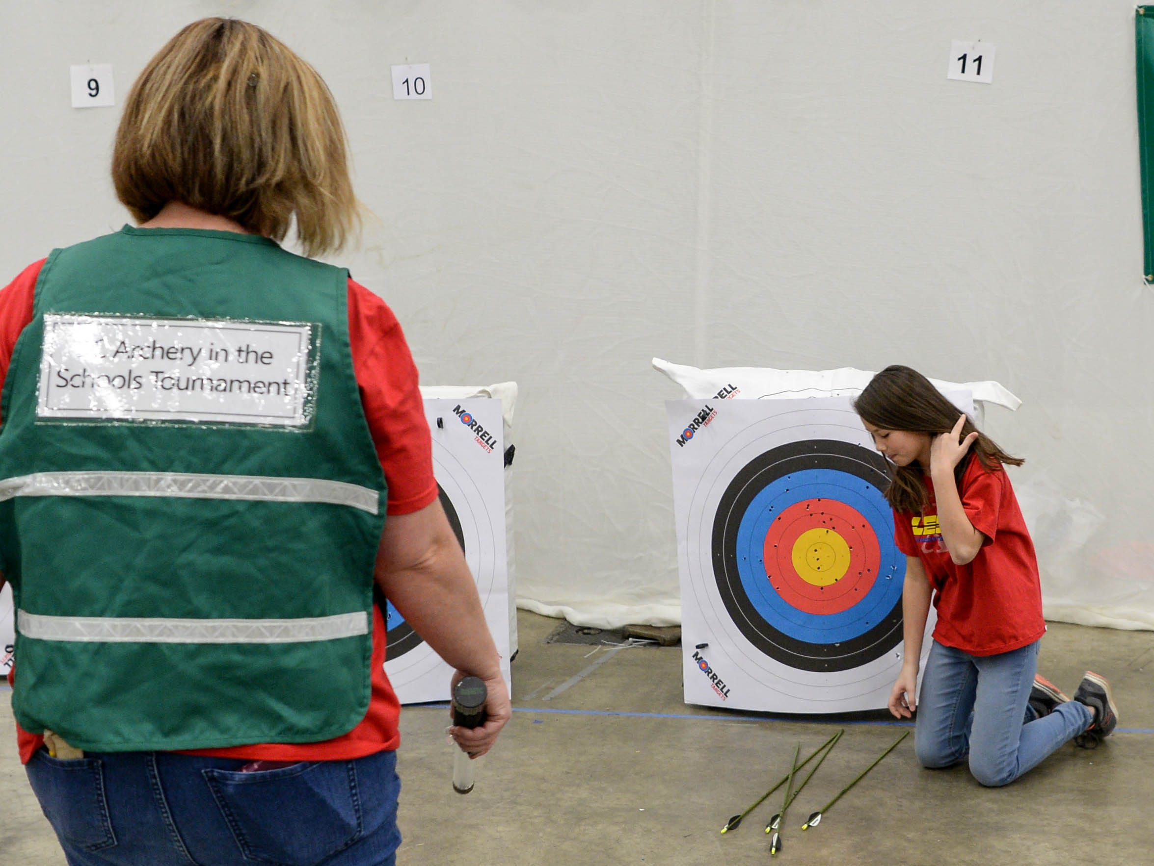 Melida Reeves, left, Pricipal at LaFrace Elementary School, approaches Jayda Masters, a fourth-grade student from her school, as she collects her arrows during the South Carolina Department of Natural Resources regional National Archery in the Schools Program (NASP) regional competition at the Anderson Civic Center Wednesday.