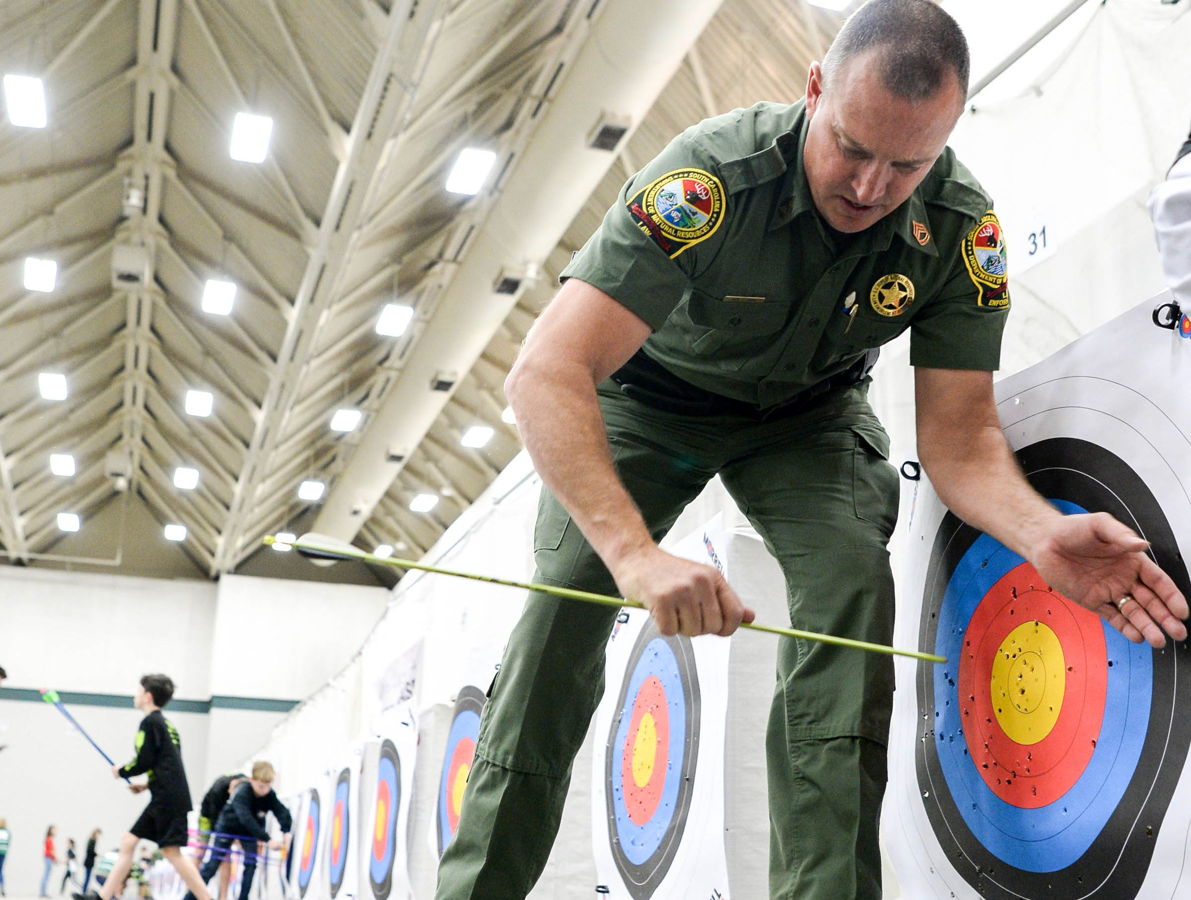 Sfc. Ken Cope helps pull out arrows during the South Carolina Department of Natural Resources regional National Archery in the Schools Program (NASP) regional competition at the Anderson Civic Center Wednesday.  The program, which awards $50,000 in scholarships to high school seniors, is a joint venture between state departments of Education and Wildlife. The competition in Anderson, leading up to the state finals March 26-28 in Sumter, had 950 children from 14 elementary and 23 high schools around the state.