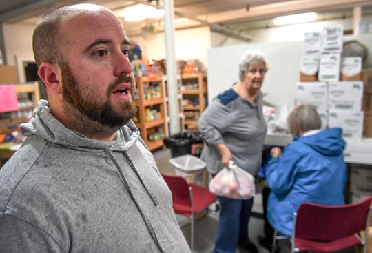 The Rev. Matthew Greer of Piedmont United Methodist Church, left, joins with volunteers and fellow church members Joy Clark, middle, and Judy Batcher, right, as they prepare baskets of food for families in need at the Piedmont Emergency Relief center in Piedmont .