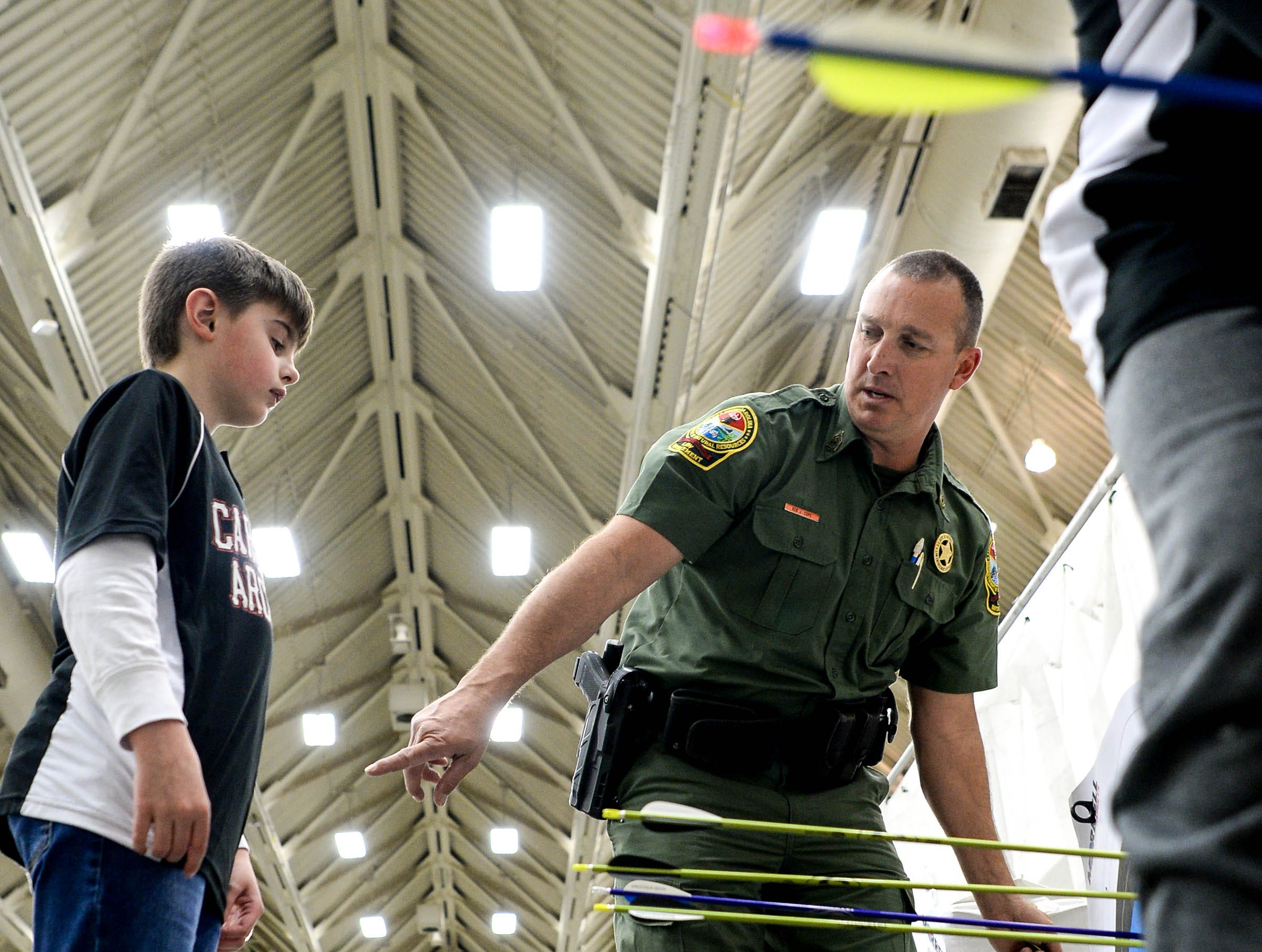 Sfc. Ken Cope helps Cooper Wilburn of Bethel Elementary School in Simpsonville pull out his arrows during the South Carolina Department of Natural Resources regional National Archery in the Schools Program (NASP) regional competition at the Anderson Civic Center Wednesday.  The program, which awards $50,000 in scholarships to high school seniors, is a joint venture between state departments of Education and Wildlife. The competition in Anderson, leading up to the state finals March 26-28 in Sumter, had 950 children from 14 elementary and 23 high schools around the state.