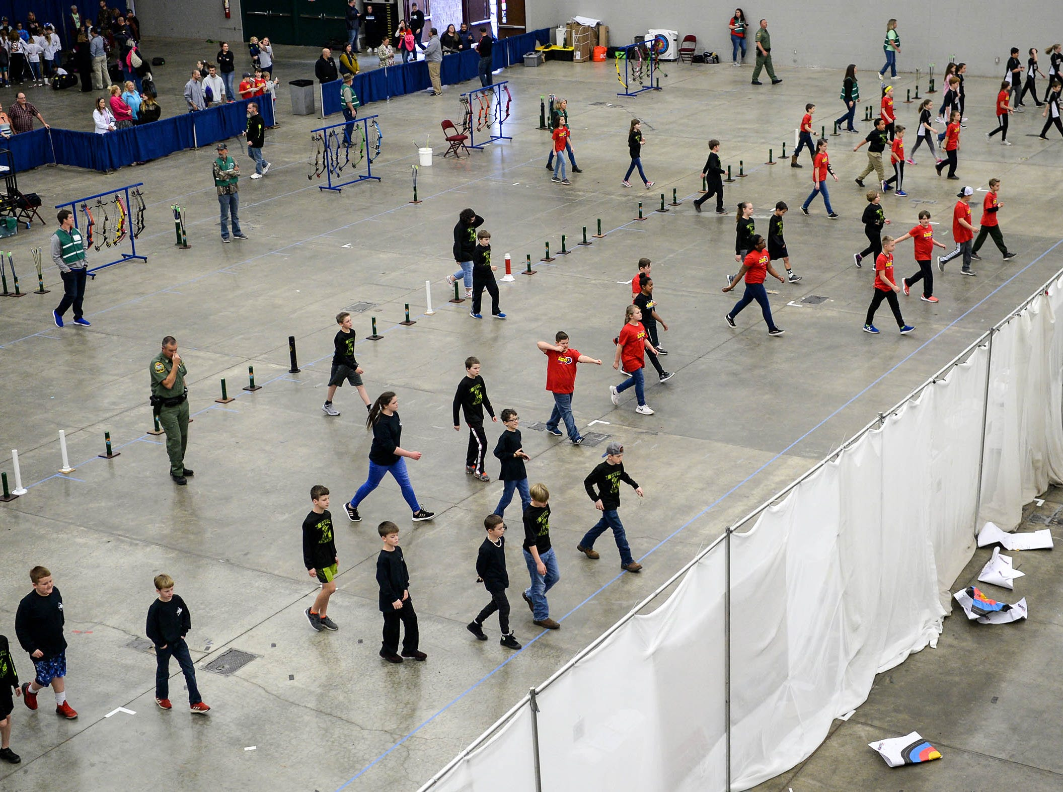 Students walk safely toward their arrows shot on targets during the South Carolina Department of Natural Resources regional National Archery in the Schools Program (NASP) regional competition at the Anderson Civic Center Wednesday.