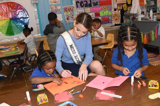 Miss Louisiana USA Victoria Paul of Alexandria (center) helps April Jones and Jaceon Bell with coloring cards and inspiration pages for veterans. Paul was visiting a class of Kindergarten students at D.F. Huddle Elementary School.