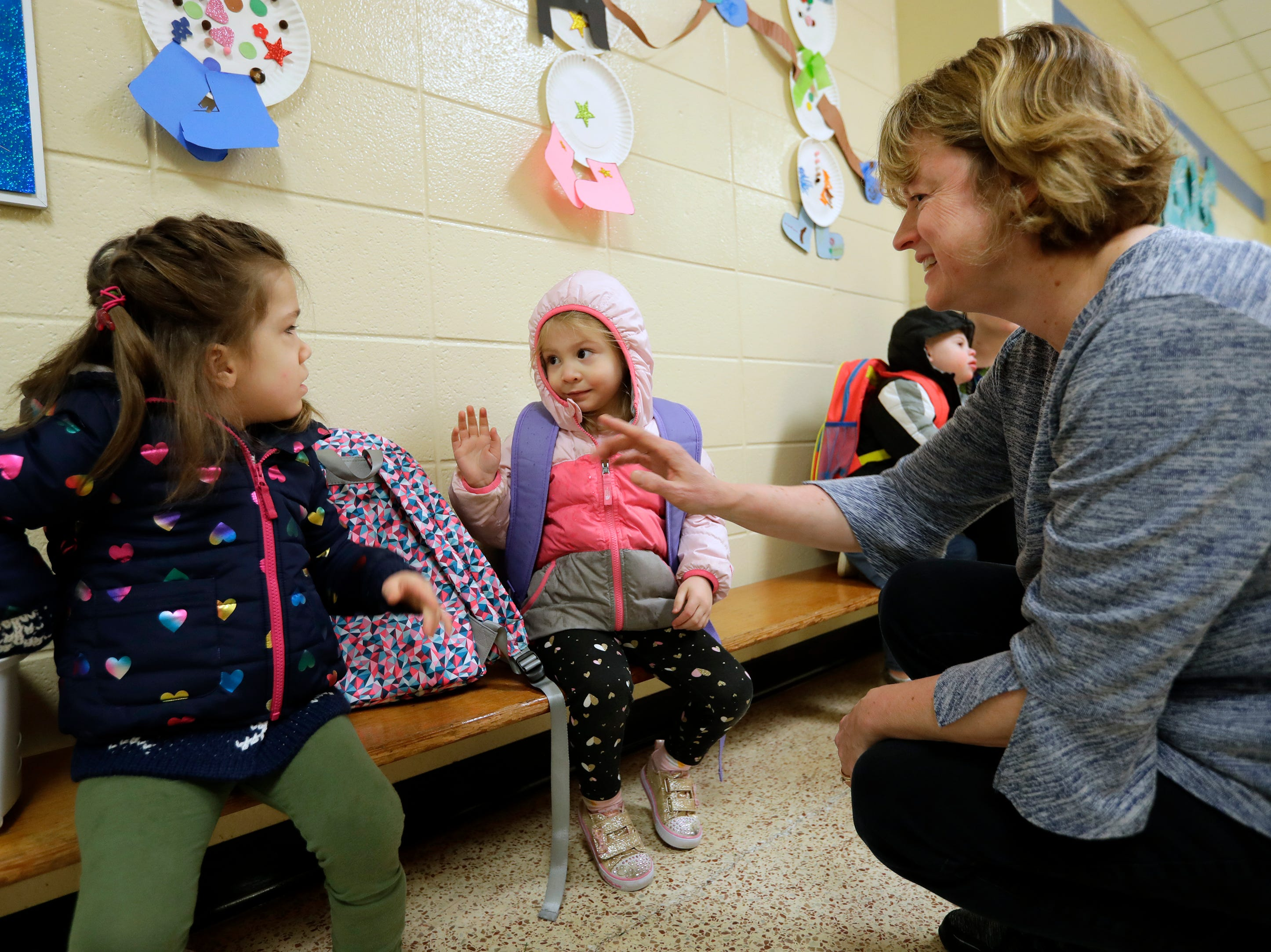 Avi Brennan, left, is a little hesitant as she is introduced to Lydia Denton, 3, on her first day of school by her teacher Renee Poeschl Monday, Jan. 7, 2019, at the Washington School of Early Learning in Neenah, Wis.