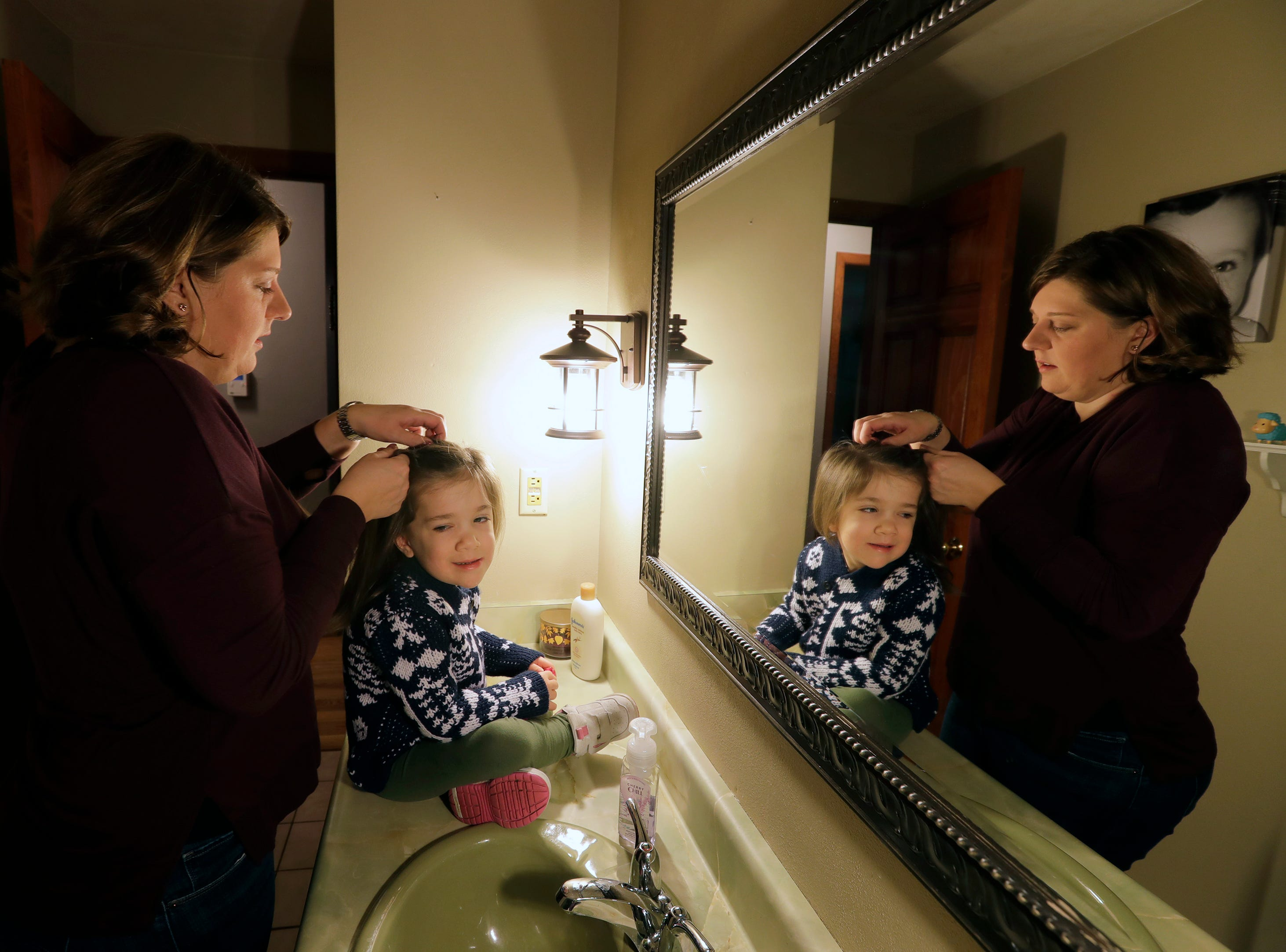 Avi Brennen, 4, gets her hair done by her mother Nina Maroszek Brennan as they prepare for her first day of school Monday, January 7, 2019, at their home in Clayton, Wis. Avi is attending Washington School of Early Learning. 
