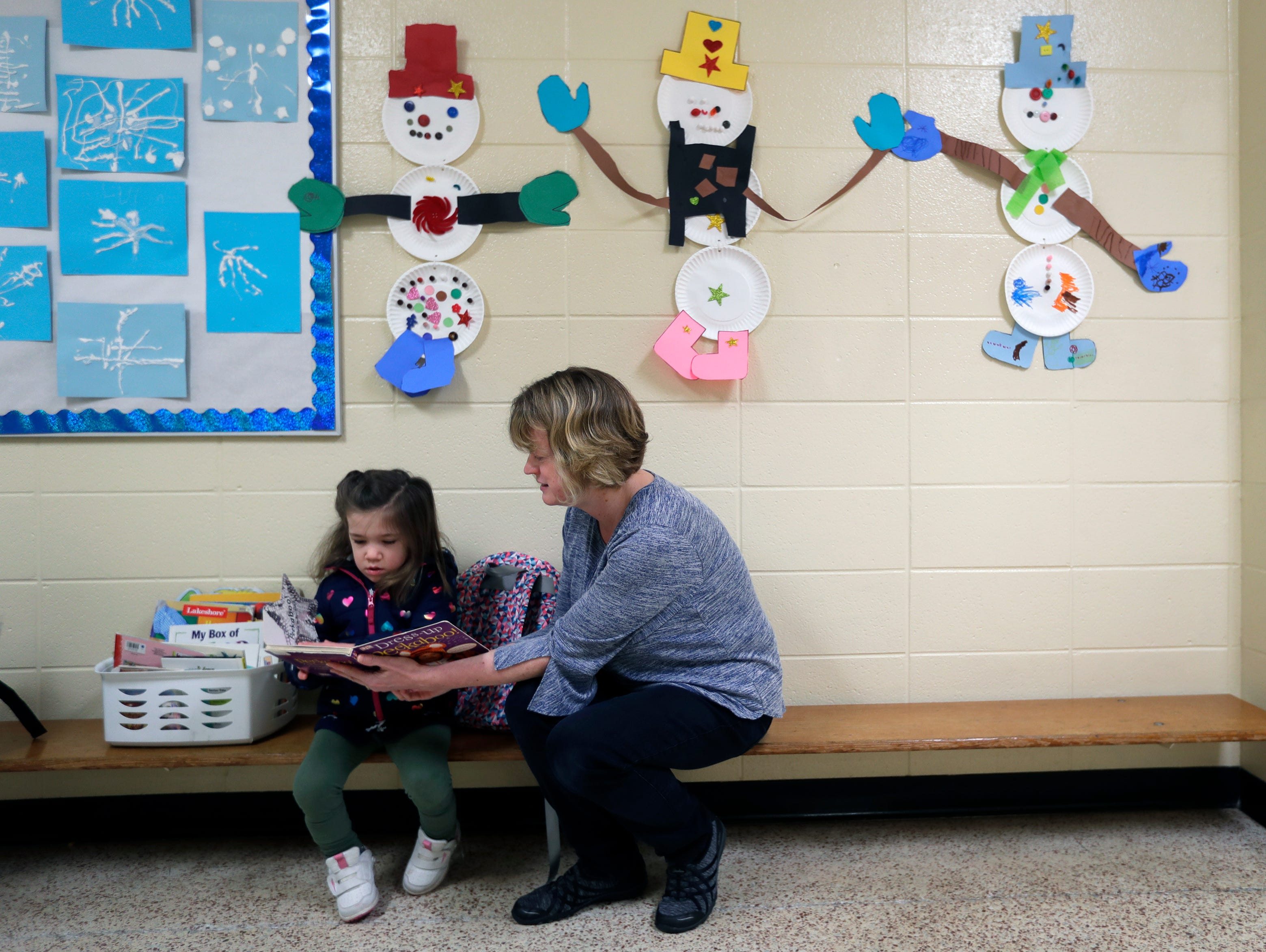 Avi Brennan, 4, looks at a book with her teacher Renee Poeschl as they wait for her classmates to arrive on her first day of school Monday, January 7, 2019, at the Washington School of Early Learning in Neenah, Wis. 