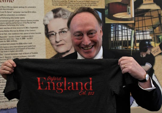 Best-selling author Andrew Richards shows off a T-shirt given to him Tuesday, a souvenir from an Abilene Christian University study abroad trip to England, where Roberts live. He gladly accepted it, though he admitted he's a Cambridge man himself.