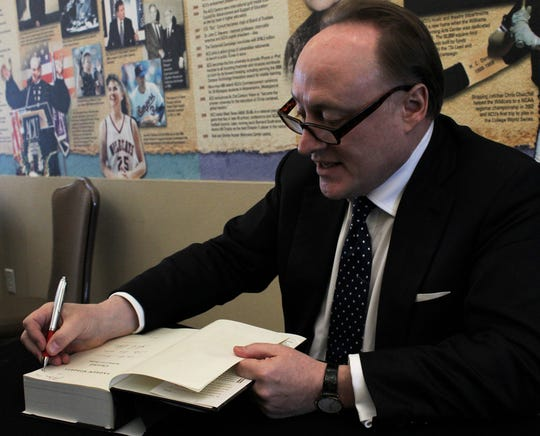 """Andrew Roberts signs a copy of his book """"Churchill: Walking With Destiny"""" for Don Drennan on Tuesday before Roberts spoke to a large Community Luncheon crowd at the Hunter Welcome Center on the Abilene Christian University campus."""