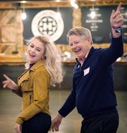 """Olivia Hughes, and John G. Pierce, Vice Chancellor for Administration and Finance at UNC Asheville, show off the progress of their dance number to """"Stayin' Alive"""" by the Bee Gees during a rehearsal for Dancing with the Local Stars at Highland Brewing on Feb. 10, 2019."""