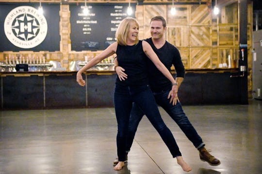 """Tracy Buchanan, CarePartners CEO, and her dance partner Jake Lavender show off the progress of their dance number to """"Love Shack"""" by the B-52's during a rehearsal for Dancing with the Local Stars at Highland Brewing on Feb. 10, 2019. Tickets are on sale for the Feb. 24 show at the Diana Wortham Theatre."""