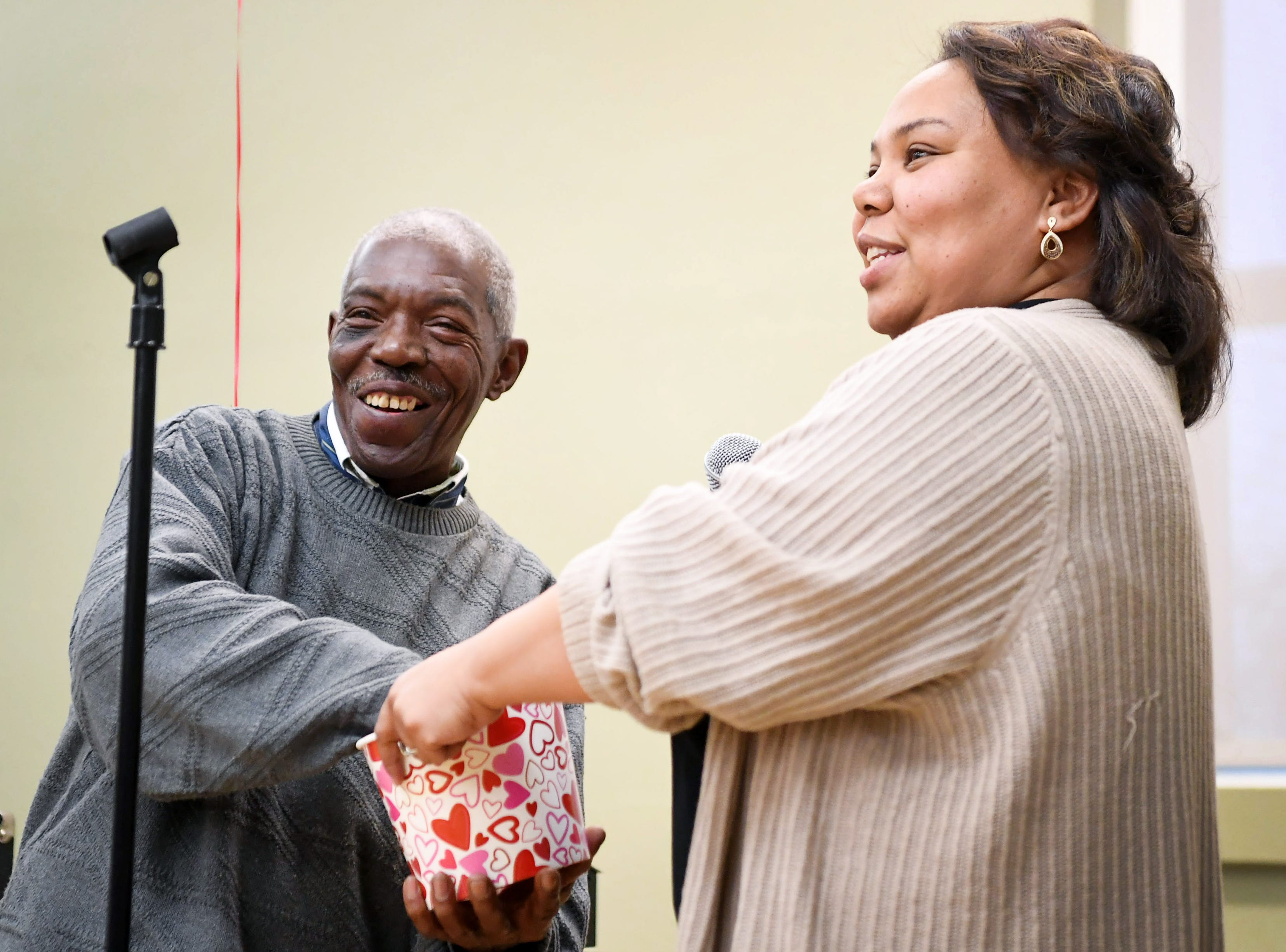 Shateisha Bowden, facility director of Burton Street, prepares to announce a door prize as emcee Harry McLaughlin draws the winner at the District 9 senior club's Valentine social at the Stephens-Lee Recreation Center in Asheville Feb. 12, 2019.