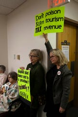 Janet Spivey and Ellie Pinkham hold signs protesting the proposed asphalt plant during the Board of Commissioners meeting. The main lecture hall at the A-B Tech Madison campus was filled to capacity and others wishing to view the meeting were put into an overflow room down the hall.