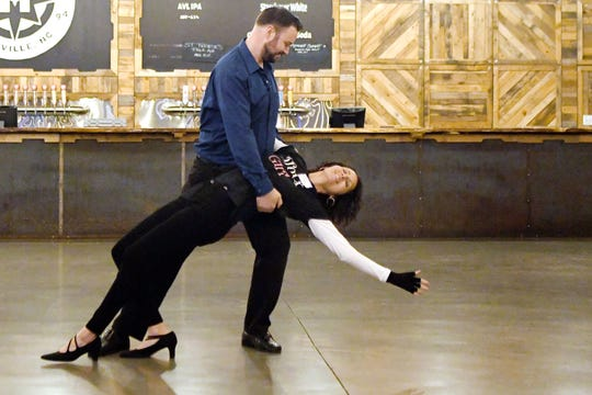 Asheville Citizen Times outdoors reporter Karen Chávez is dipped by her dance partner, Jason Barnes, as they show off the progress of their dance during a rehearsal for Dancing with the Local Stars at Highland Brewing on Feb. 10, 2019. Chávez is a breast cancer survivor and is dancing for her aunt, Audrey, who died after a battle with colon cancer.
