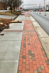 The new sidewalks in Fletcher, part of a $2.1 million improvements package, include concrete and brick work.