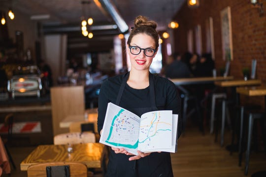 Eugenie Zynda holds the official Restaurant Week book inside The Shop in downtown Binghamton March 16, 2017.