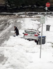 Snow is removed from around cars parked along Sidney Avenue in Bremerton on Wednesday.