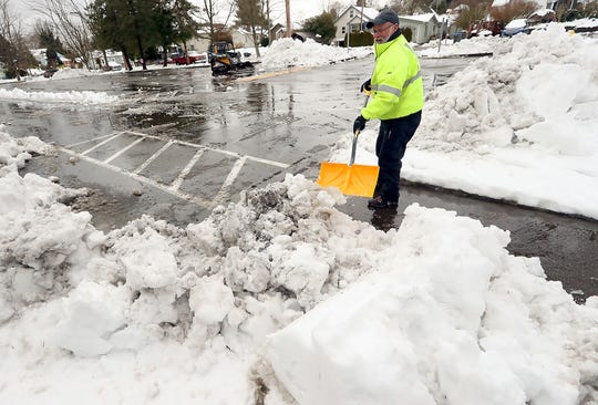 Lance McCoy, head groundskeeper for the Bremerton School District, shovels out the sidewalks after clearing one of the parking lots at Bremerton High School on Wednesday, February 13. 2019.
