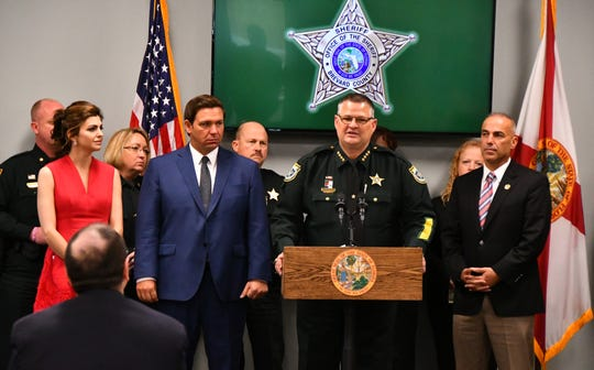 Governor Ron DeSantis, accompanied by First Lady Casey DeSantis, left, and Andrew Pollack, right, was in Brevard  Wednesday at the Deputy Barbara Pill Law Enforcement Facility in Titusville. Standing with Sheriff Wayne Ivey, center, with Ivey's command staff behind them, Gov.  DeSantis issued an executive order with a series of steps designed to further improve safety in Florida's schools. Andrew Pollack's daughter Meadow was killed a year ago in the Parkland school shooting.