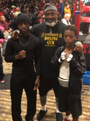 Alex Bray, right, with his brother Kamar Bray and his father, coach Robert Bray. Alex was the runner-up for a Silver Gloves national championship recently in Missouri.