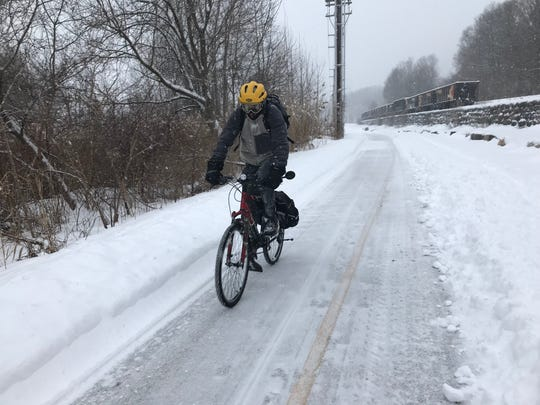 A cyclist braves a winter storm warning and pedals down the Burlington Bike Path on Wednesday morning, Feb. 13, 2019.