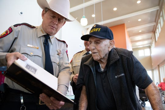 Nueces County Sheriff J.C. Hooper shows 93-year-old Edward 'Eddie' Ogdee a book with all the past sheriffs from Texas counties on Wednesday, Feb. 13, 2019. Ogdee served as the sheriff of Brooks County in the 1970s.