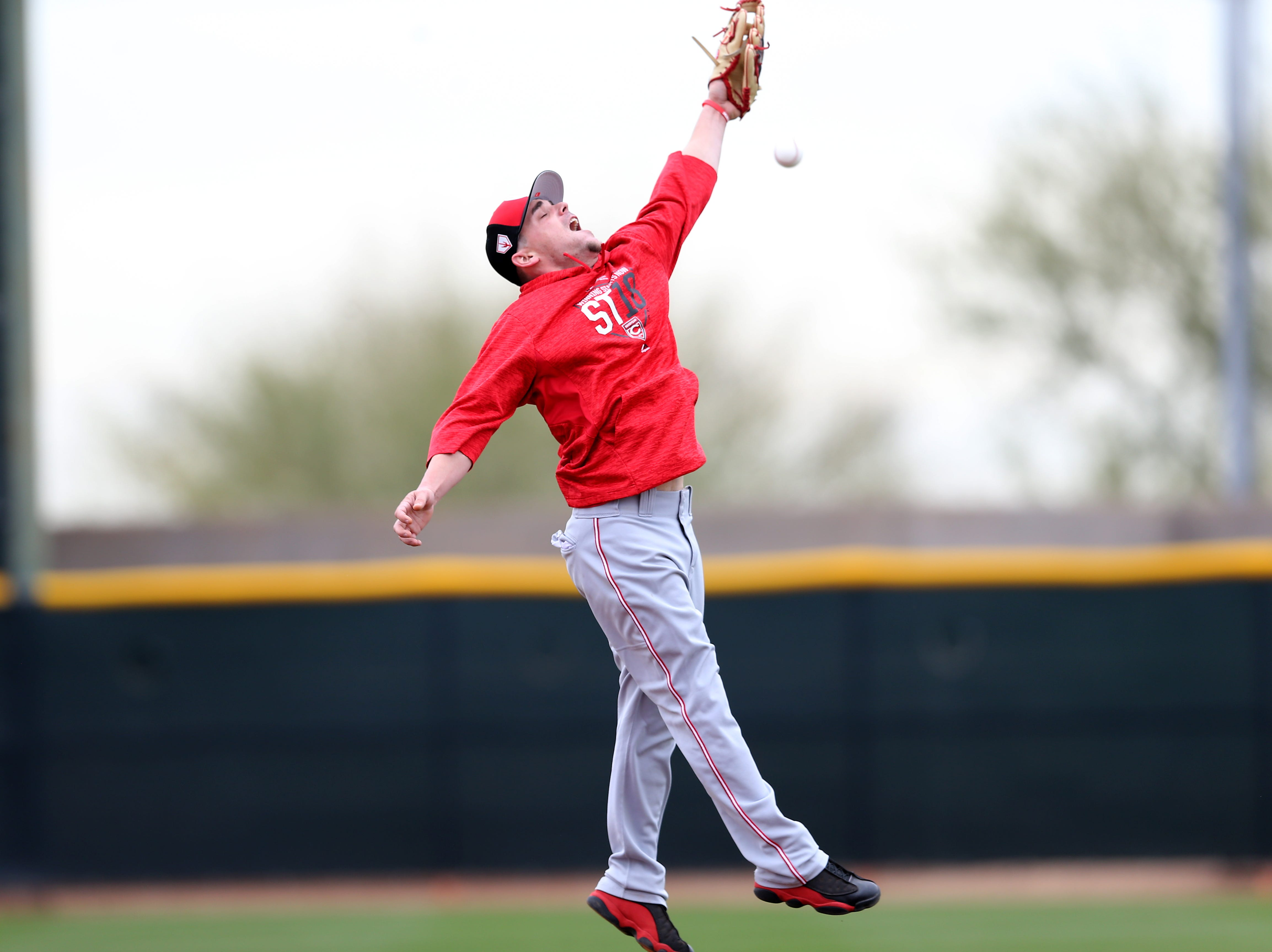 Cincinnati Reds second baseman Scooter Gennett (3) leaps for a ball during drills, Wednesday, Feb. 13, 2019, at the Cincinnati Reds spring training facility in Goodyear, Arizona.