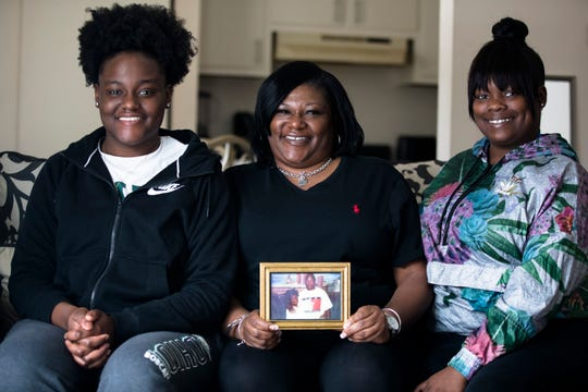 Alisia Hendricks, center, sits with her daughters, Nadeige Collier, left, and Keziah Hendricks, on Sunday, Feb. 10, 2019, at their residence in Hamilton. Alisia Hendricks' fiance and father of her children, Damon Collier, died 18 years ago due to a gunshot wound.