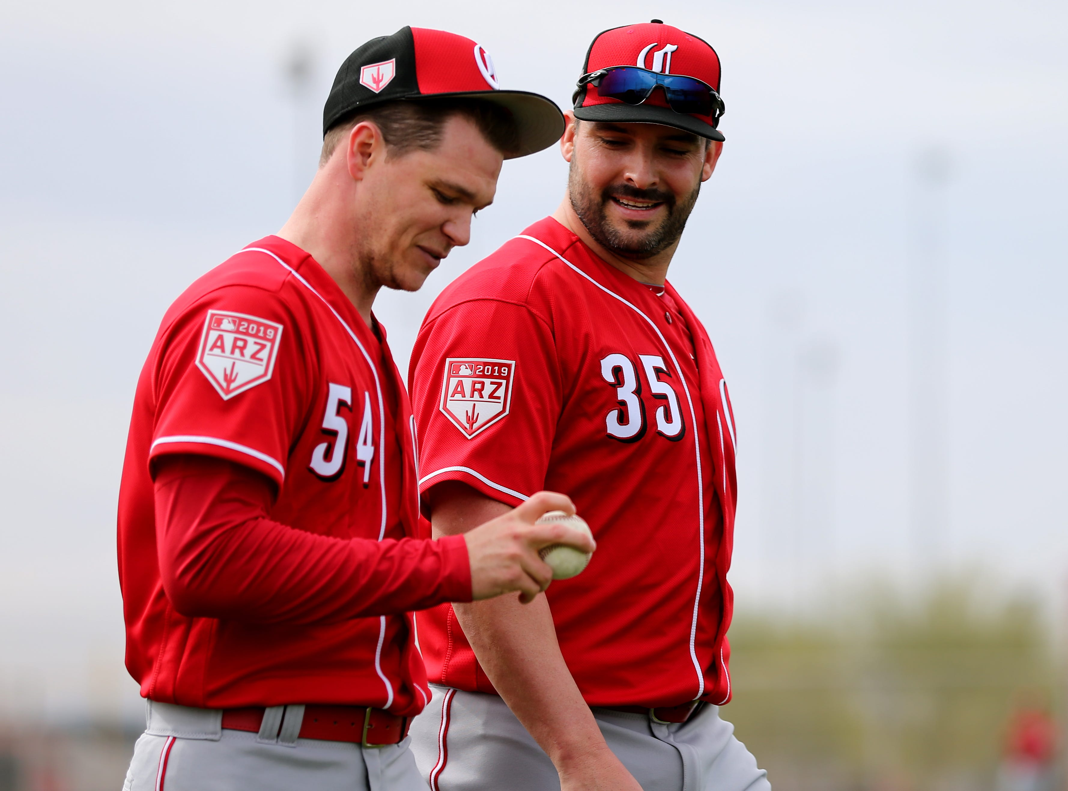 Cincinnati Reds pitchera Sonny Gray (54), left, and Tanner Roark (35), right, walk off the field after long-toss drills, Wednesday, Feb. 13, 2019, at the Cincinnati Reds spring training facility in Goodyear, Arizona.