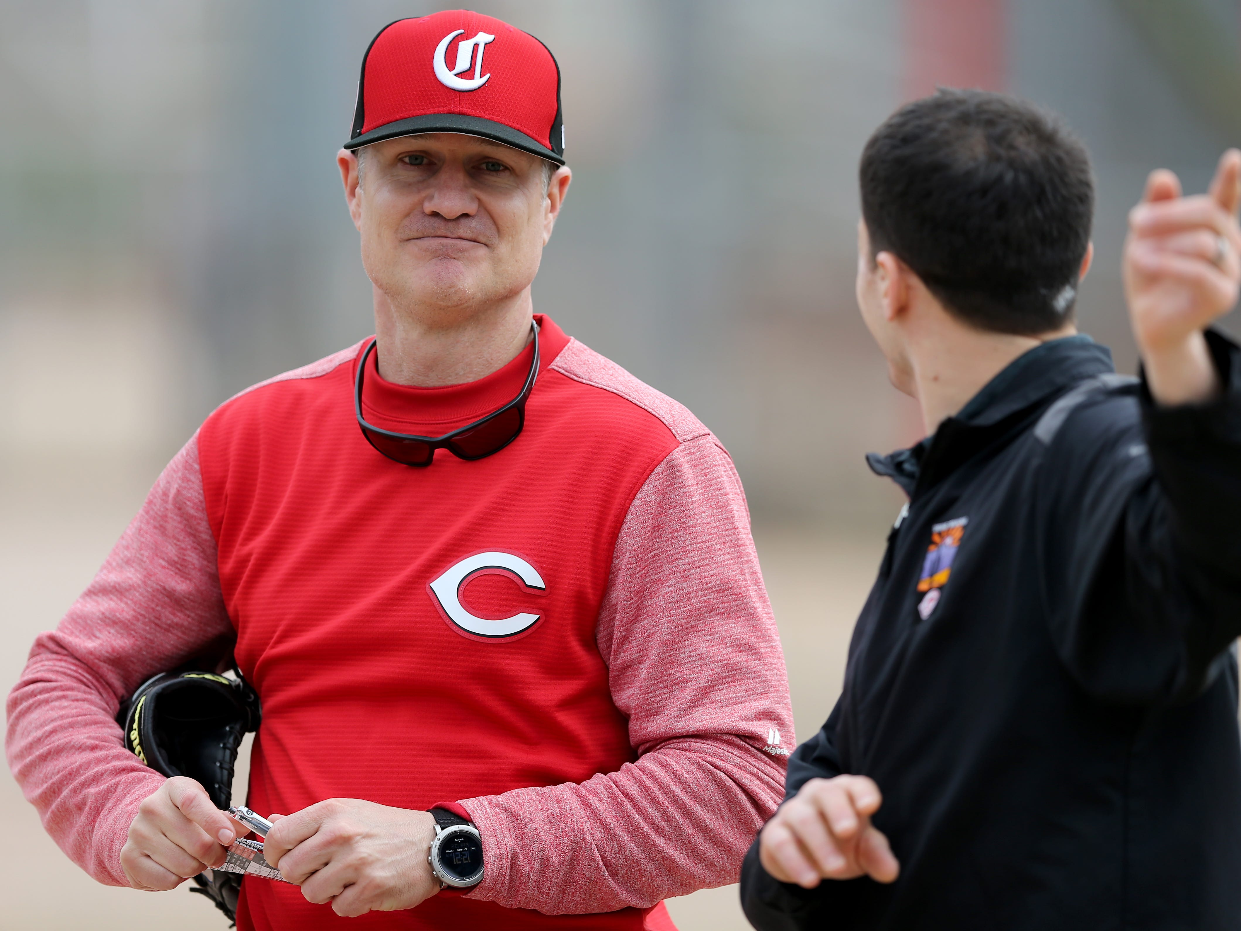 Cincinnati Reds manager David Bell (25) talks with assistant general manager Sam Grossman, right, Wednesday, Feb. 13, 2019, at the Cincinnati Reds spring training facility in Goodyear, Arizona.