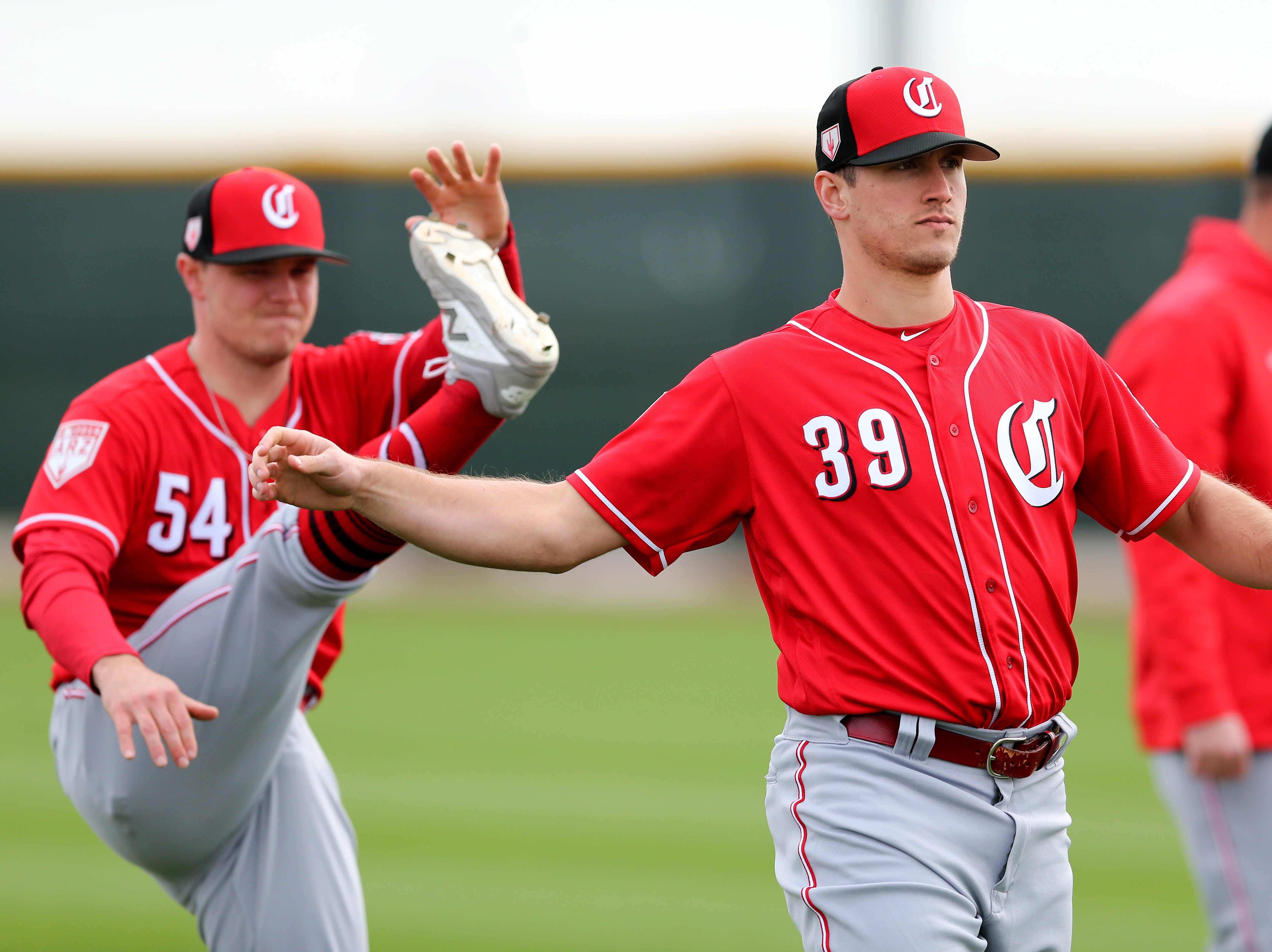 Cincinnati Reds pitchers Sonny Gray (54), left, and Lucas Sims (39), right, stretch, Wednesday, Feb. 13, 2019, at the Cincinnati Reds spring training facility in Goodyear, Arizona.