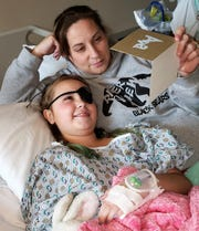Melissa Winner shares a card with her daughter Ava, who was diagnosed with a brain tumor in early January. She sometimes wears an eye patch to help her focus her vision since undergoing surgery to remove the tumor from near her brain stem.