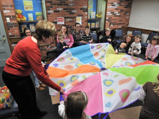 Deborah Crowdy leads preschool students in a parachute game during the Count on Reading program at the Coshocton Public Library.