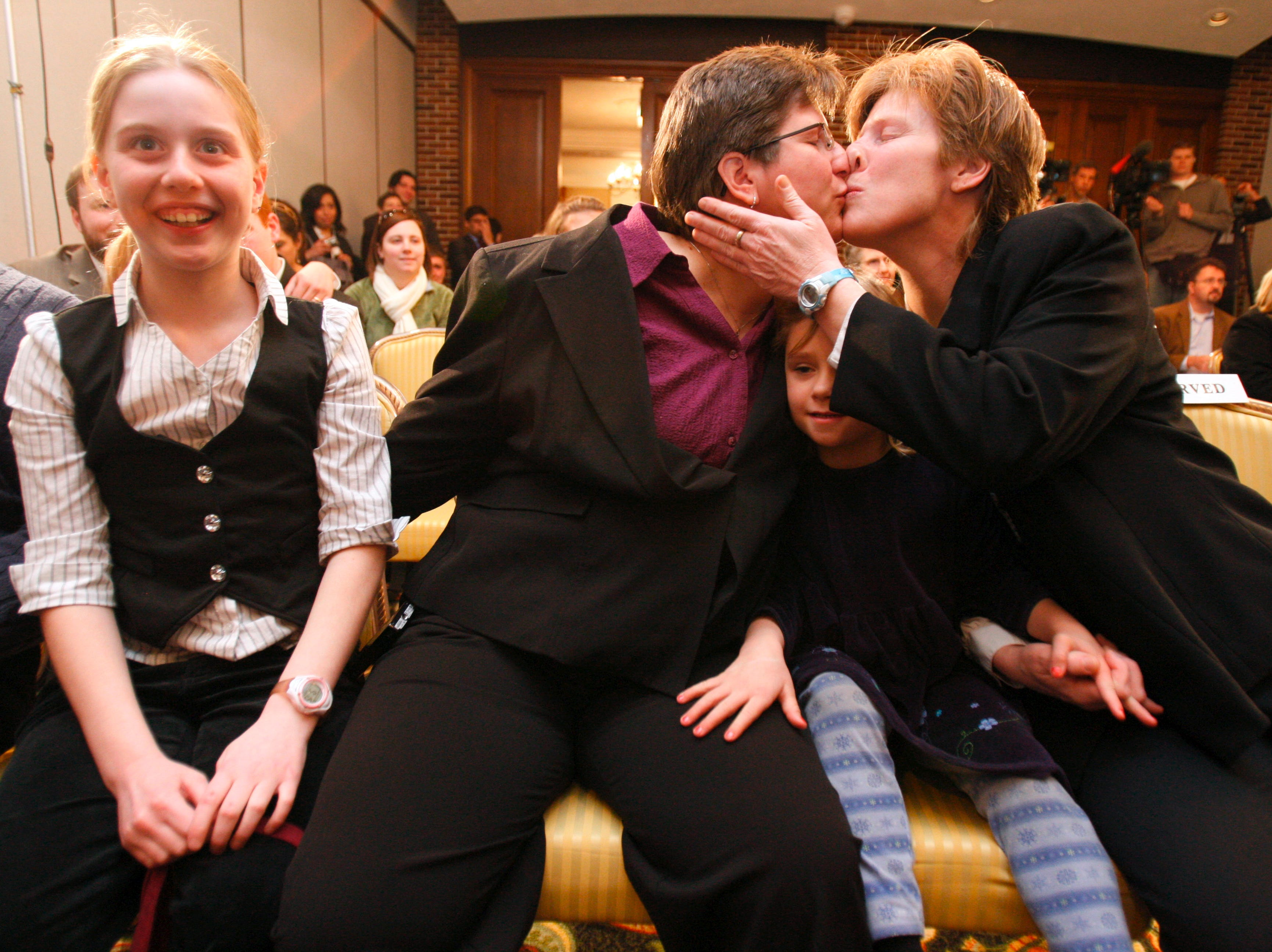 Dawn BarbouRoske, second from left, of Iowa City, kisses her partner, Jen BarbouRoske, after learning of the Iowa Supreme Court ruling in favor of legalizing gay marriage in Iowa on Friday, April 3, 2009 in Des Moines.  Between them is their daughter Bre, 6. Their other daughter, McKinley, 11, reacts to the ruling a left. (Christopher Gannon/The Des Moines Register)